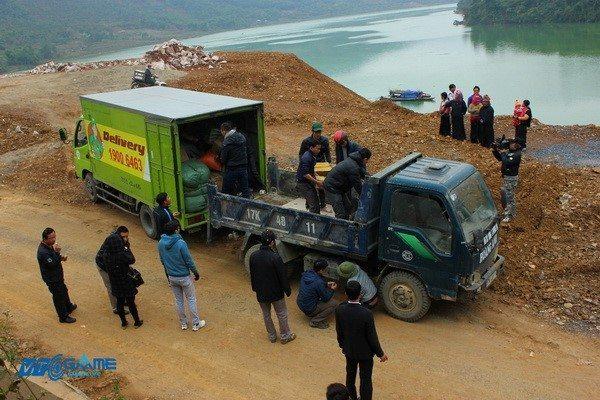Chuyển quà sang xe tải gầm cao để vượt qua con đường sạt lở vào xã Nậm Pì